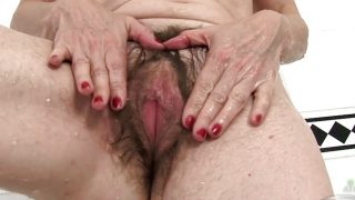 Madura en la bañera masturba su coño peludo